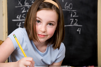 Young girl at school desk working math problems